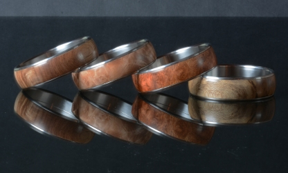 four rare wood and stainless steel bangles